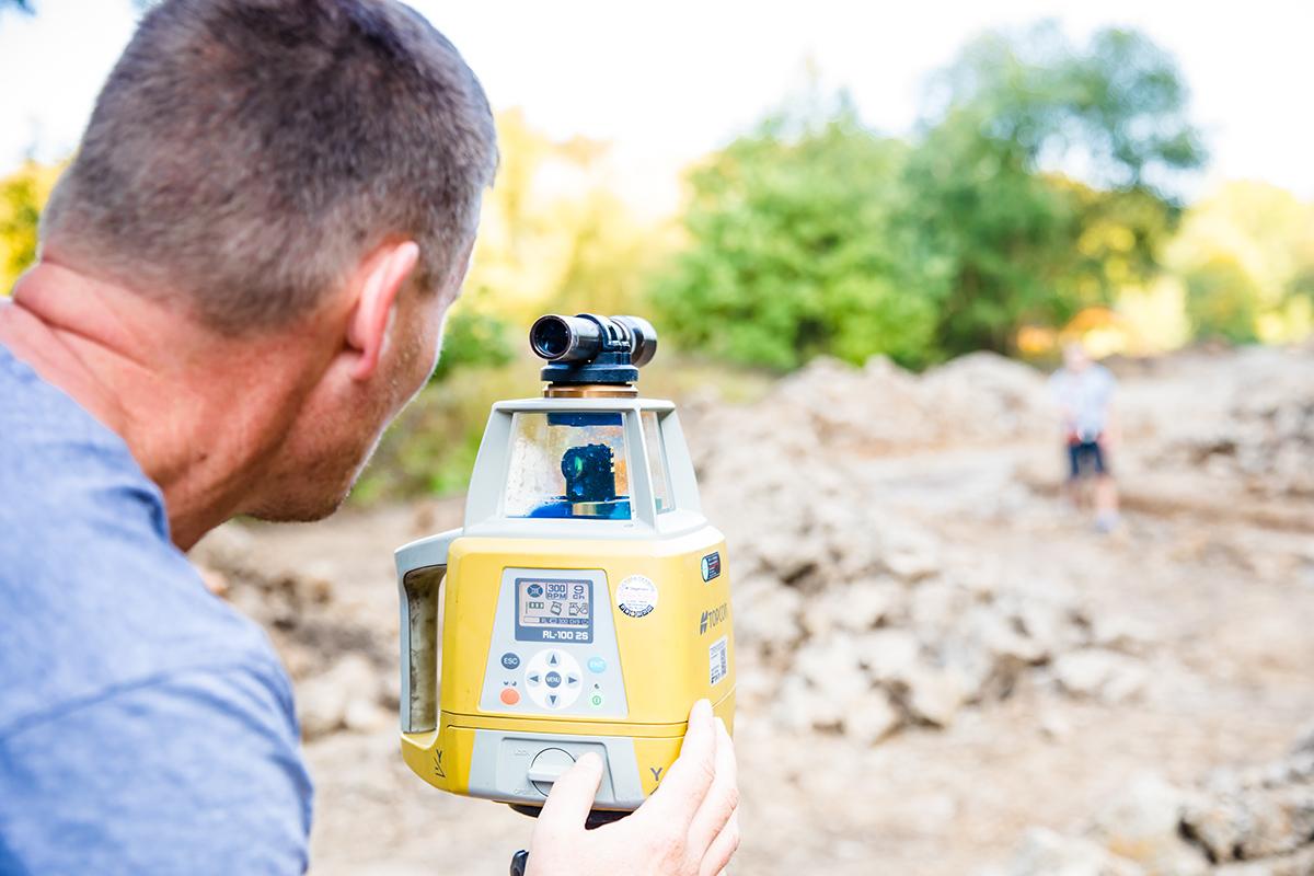 Mitarbeiter der Lodenkemper GmbH führen eine GPS-Vermessung bei Erdarbeiten durch.